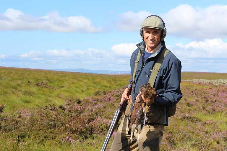 Sean with his grouse and the hills in the background